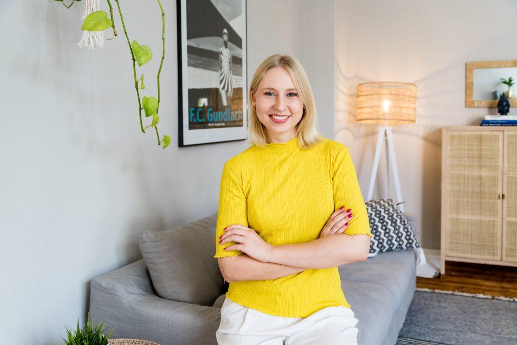 Caroline Preuss in einer Wohnung, auf einem Sofa sitzend