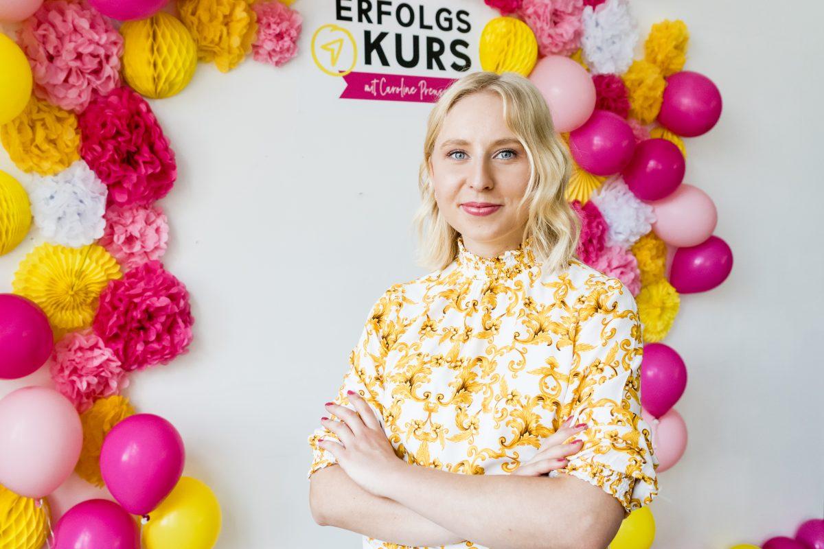 """Caroline Preuß vor einer Wand mit der Aufschrift """"Erfolgskurs"""" und Luftballons"""