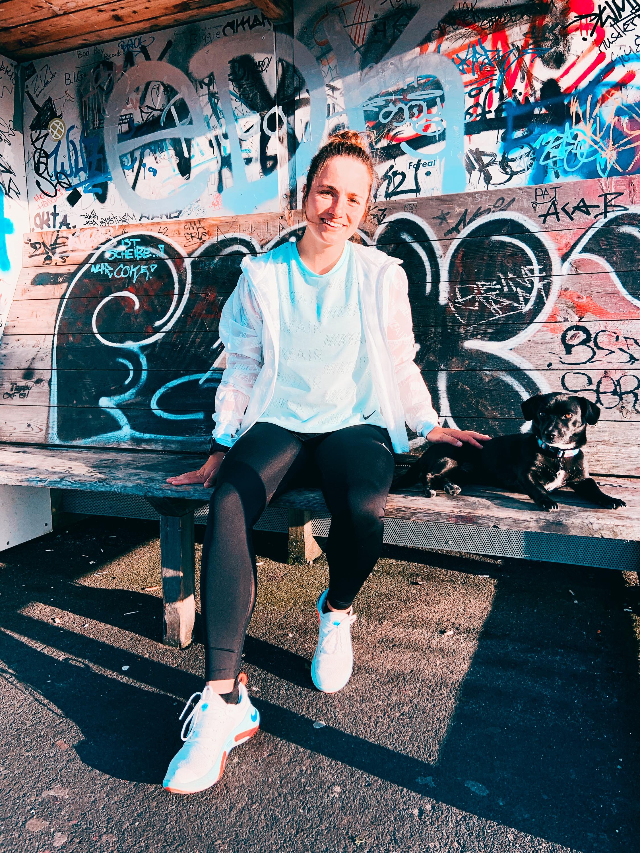 Susann Lehmann von runskills.de, sitzend vor einer Graffiti-Wand