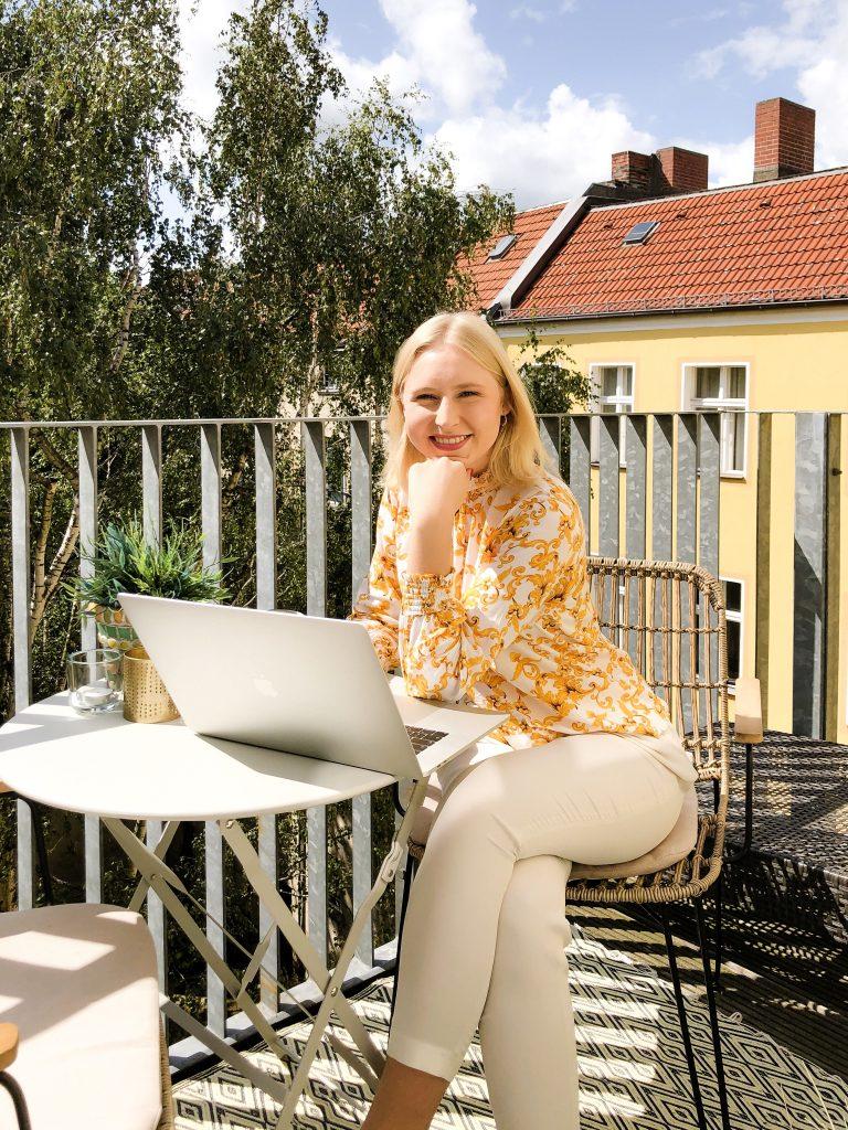 Caroline Preuß, im Freien an einem Tisch sitzend mit einem Laptop