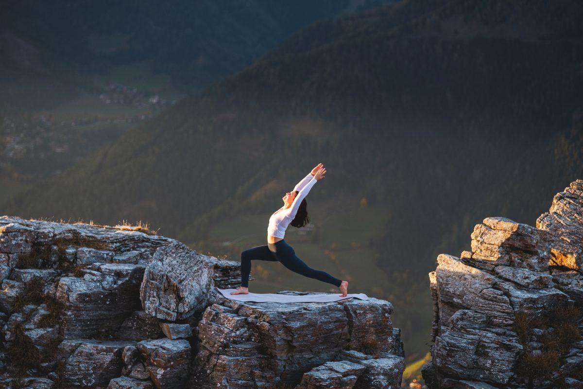 Klara Fuchs in Warrior 1 Yoga Pose, auf einem Felsen in den Bergen