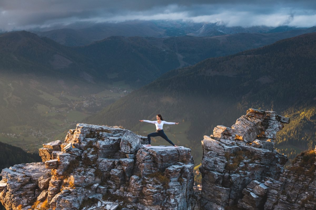 Klara Fuchs in Warrior 2 Yoga Pose, auf einem Felsen in den Bergen