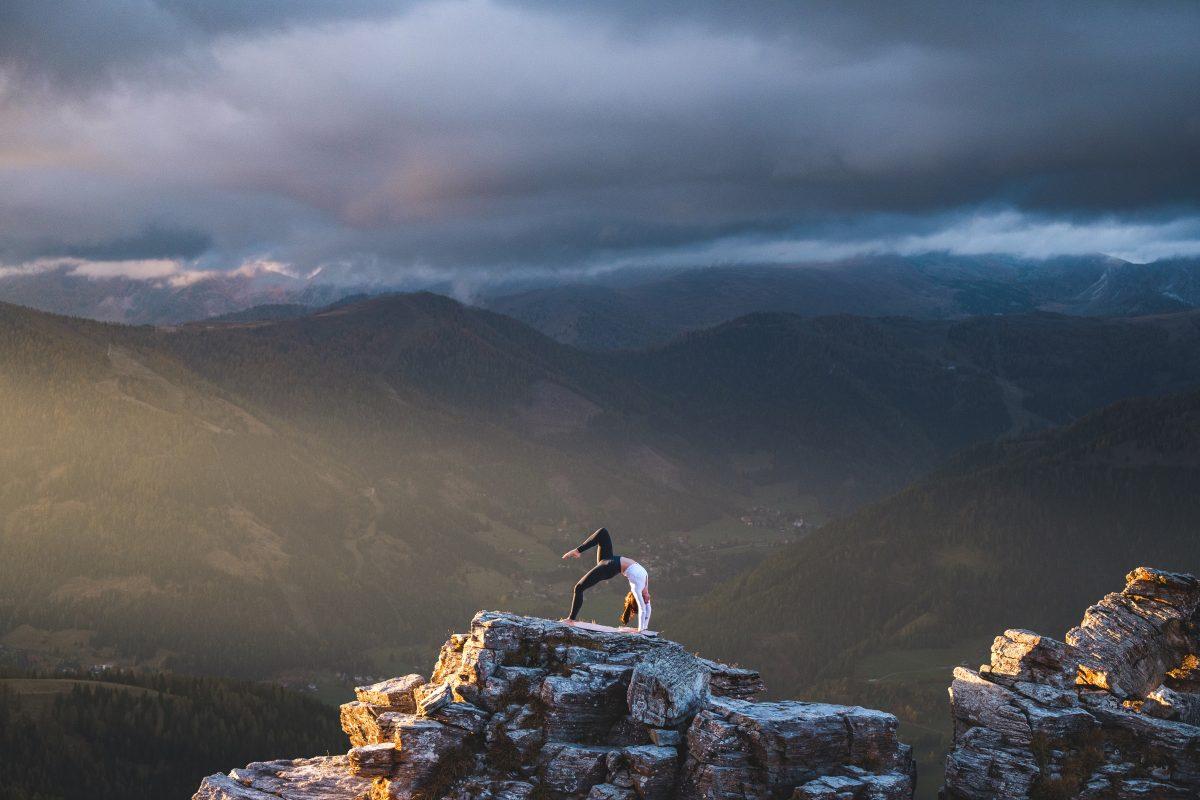 Klara Fuchs in Bridge Yoga Pose, auf einem Felsen in den Bergen