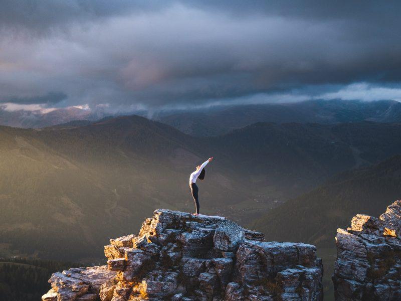 Klara Fuchs in Rückwärtsbeuge, auf einem Felsen in den Bergen