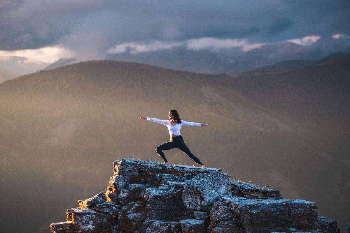 Klara Fuchs in Warrior Yoga Pose, auf einem Felsen in den Bergen