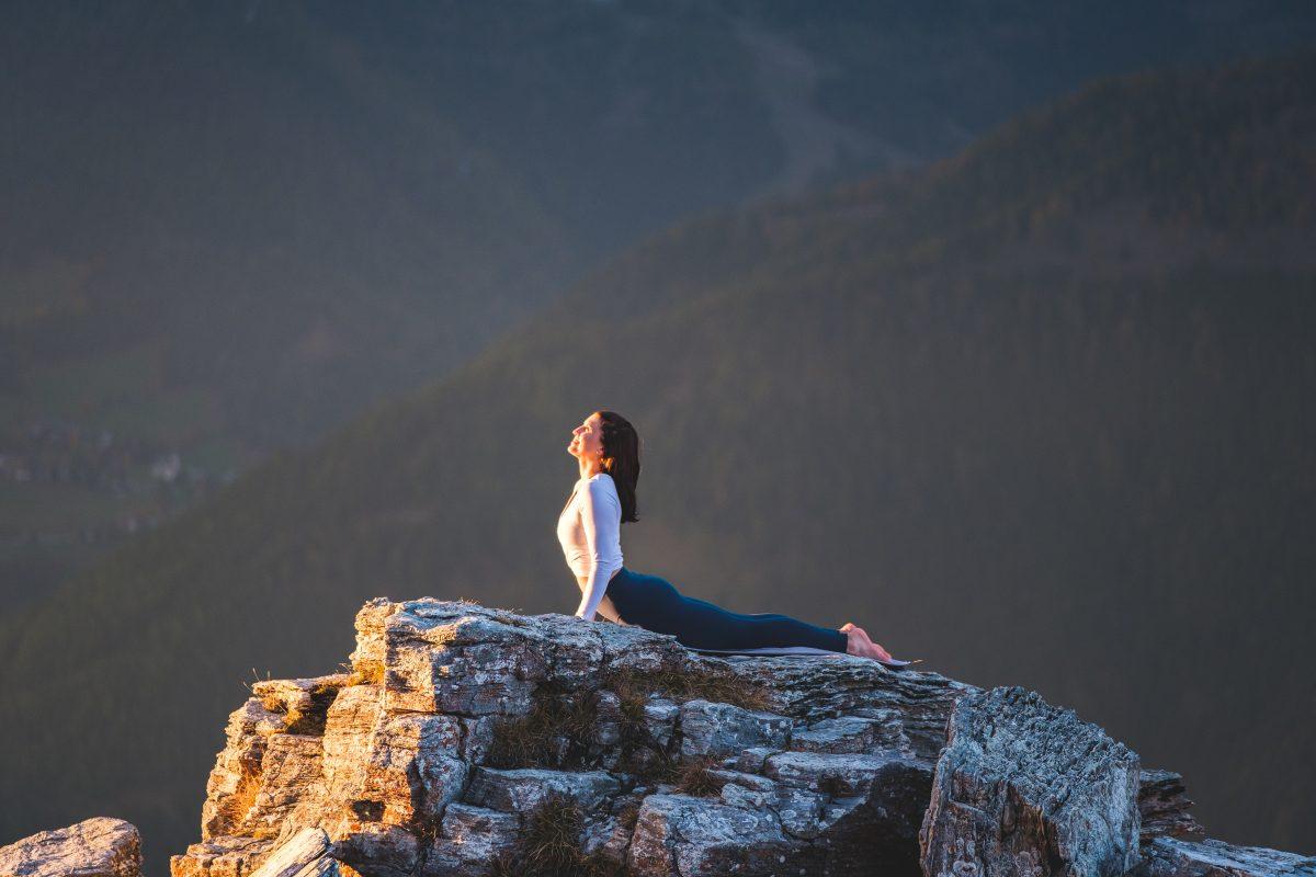 Klara Fuchs in Cobra Yoga Pose, auf einem Felsen in den Bergen
