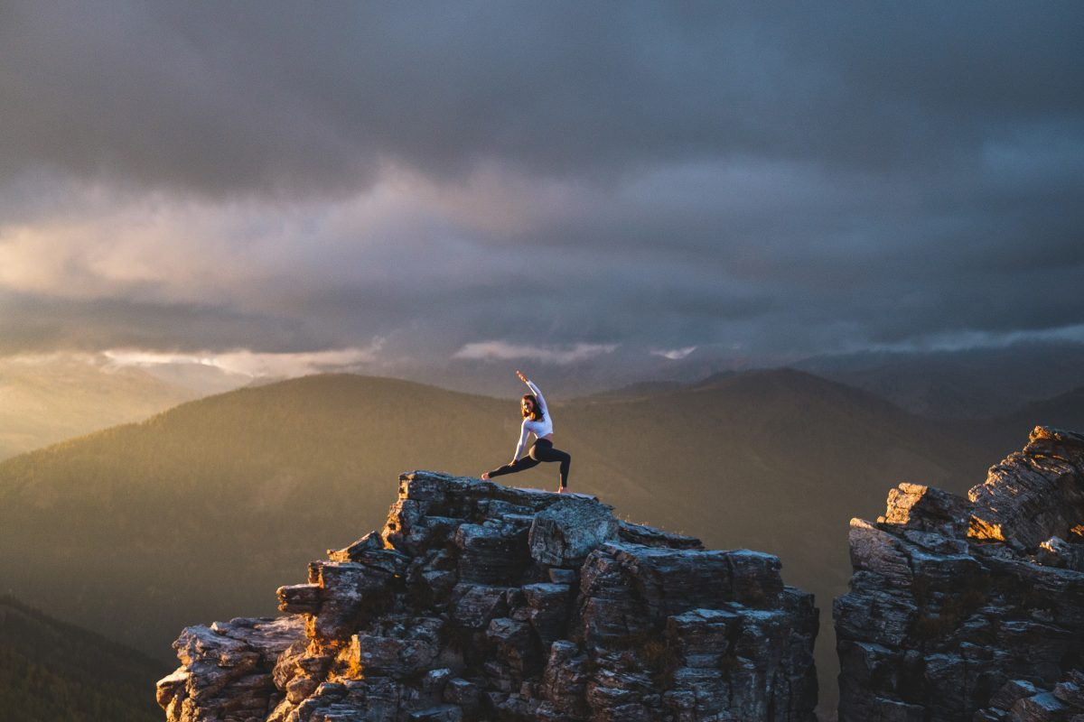 Klara Fuchs in Yoga Pose, auf einem Felsen in den Bergen