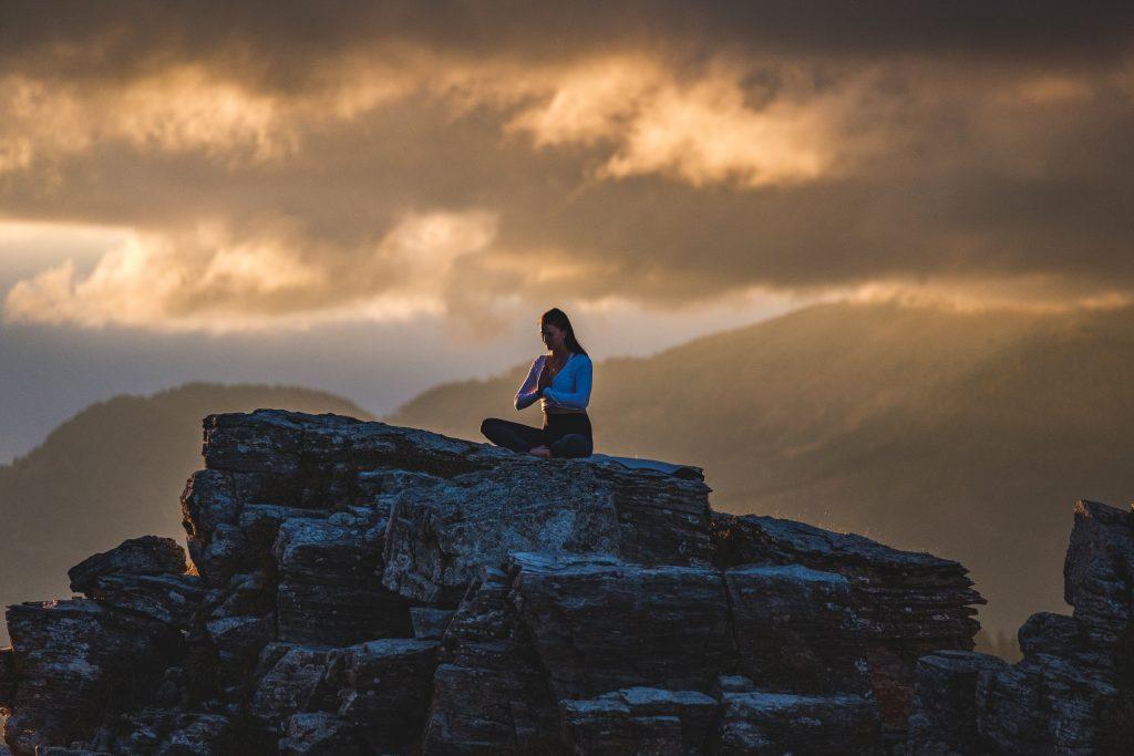 Klara Fuchs in Yoga Pose im Schneidersitz, auf einem Felsen in den Bergen