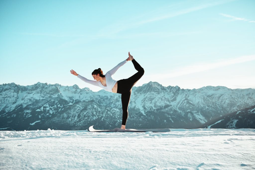 Klara Fuchs in Yoga-Pose in winterlicher Berglandschaft