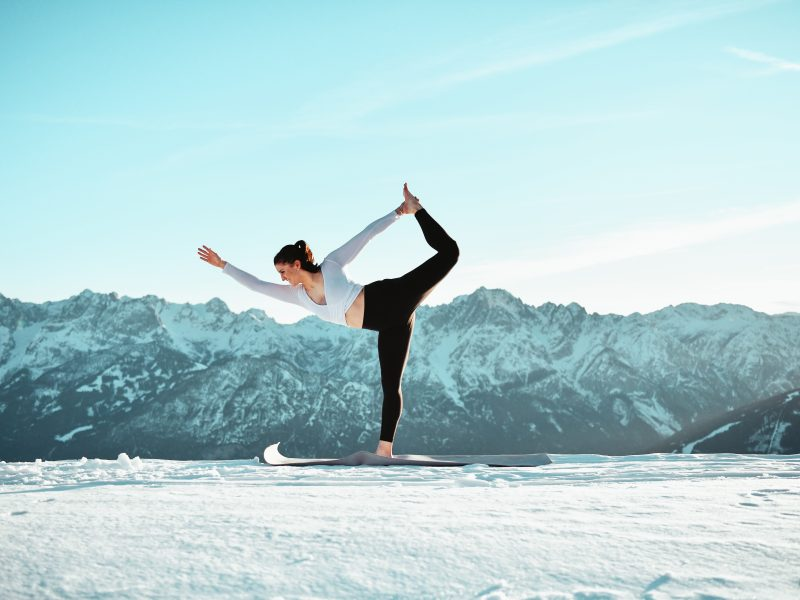 Klara Fuchs in Yoga-Pose in winterlicher Berglandschaft