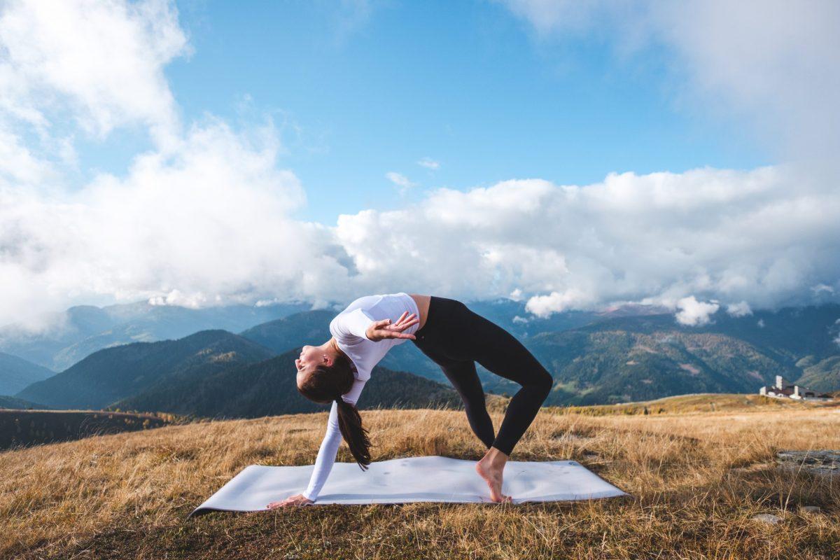 Klara Fuchs in Yogaposition Brücke vor einer Bergkulisse